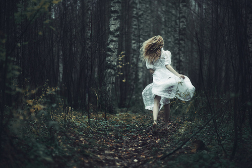 girl-running-through-a-wood-in-a-white-dress